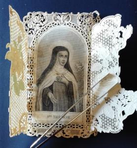 Sollevando i due lembi mobili, anch'essi traforati a punzone, appare un'incisione in acciaio raffigurante Santa Teresa